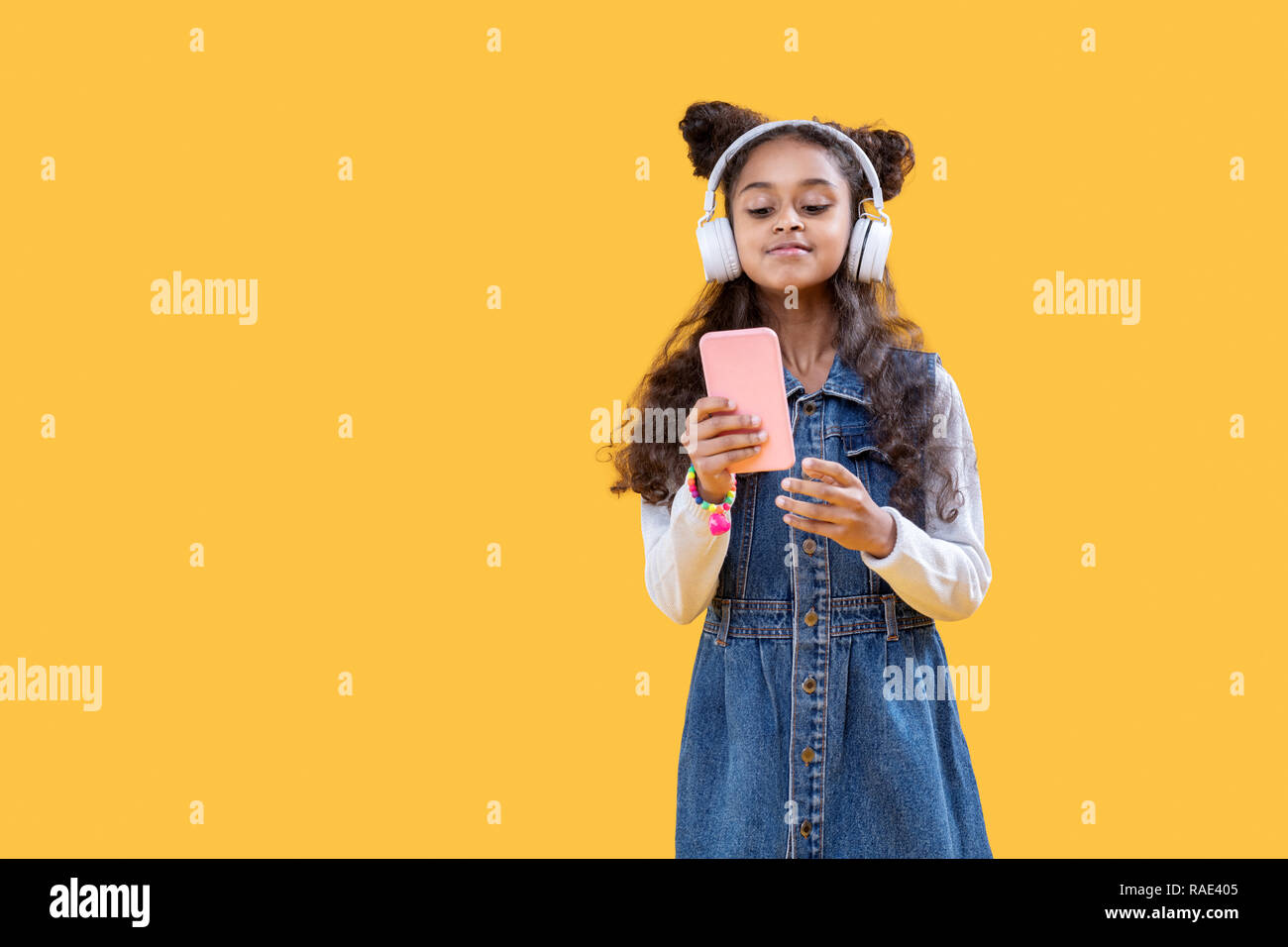 Nice afro American girl looking through her music playlist - Stock Image