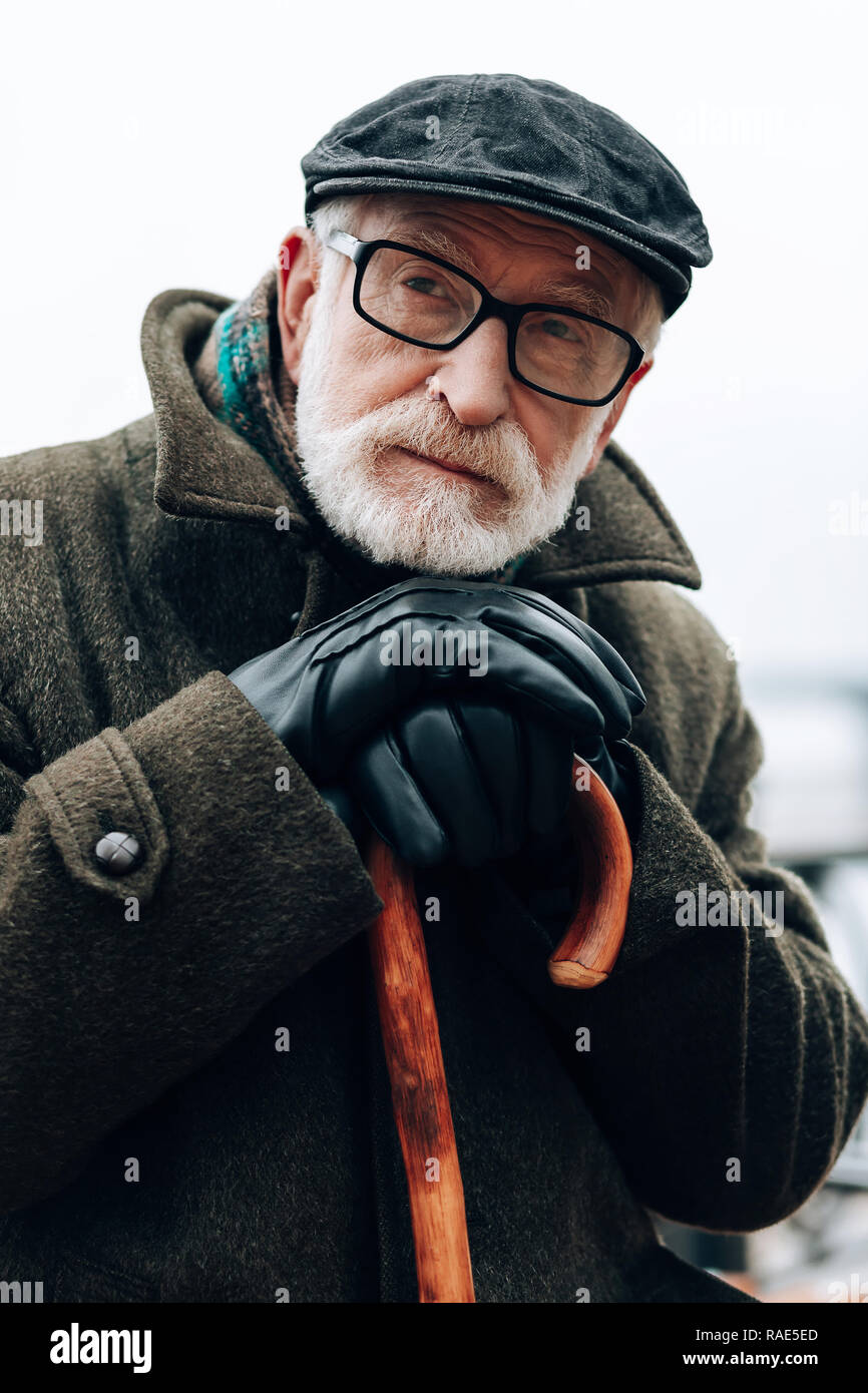 Serious pensioner being deep in his thoughts - Stock Image