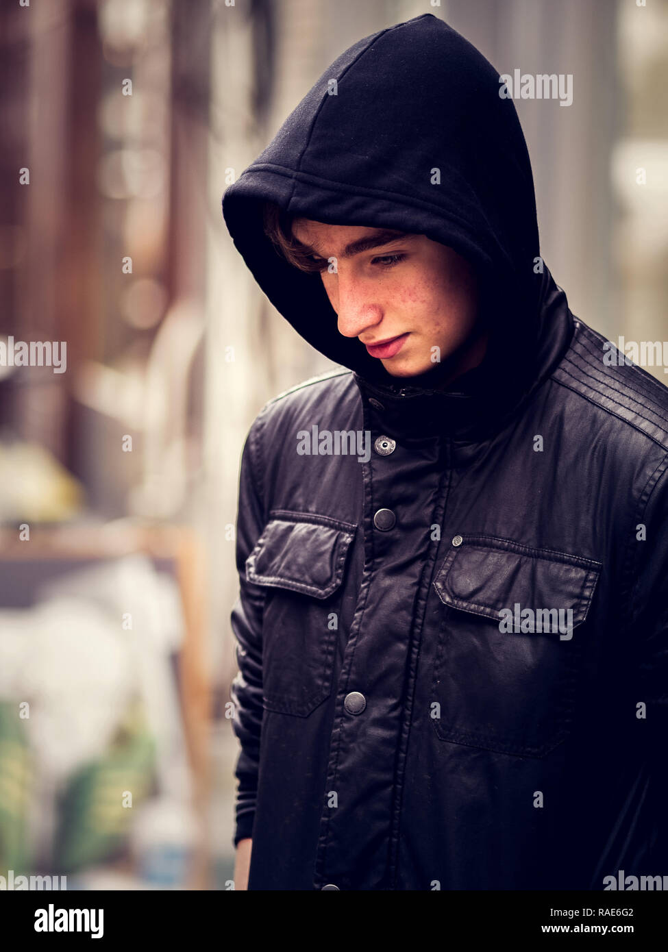 Close up young boy in black hoody with soft background - Stock Image