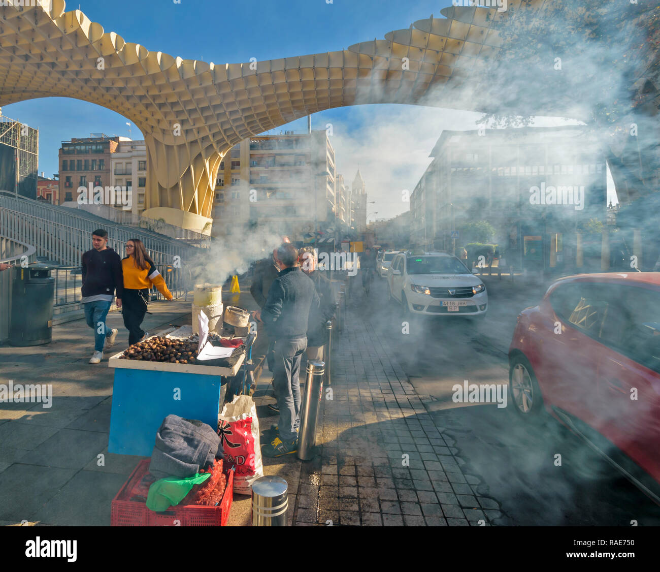 METROPOL PARASOL ENCARNACION SQUARE  SEVILLE SPAIN EARLY MORNING SMOKE FROM ROAST CHESTNUT SELLER AND PASSING TRAFFIC Stock Photo