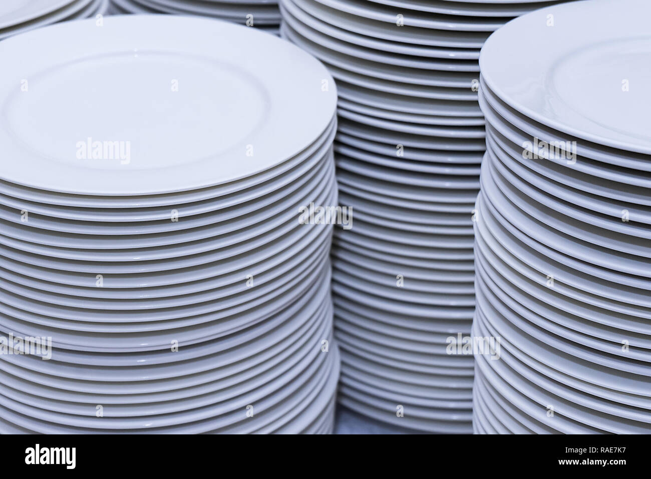 large stacks of clean white plates after washing in the kitchen - Stock Image