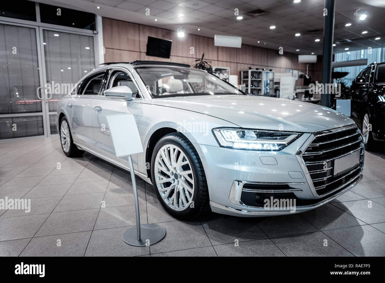 White passenger car being for disposal in nice modern car showroom - Stock Image
