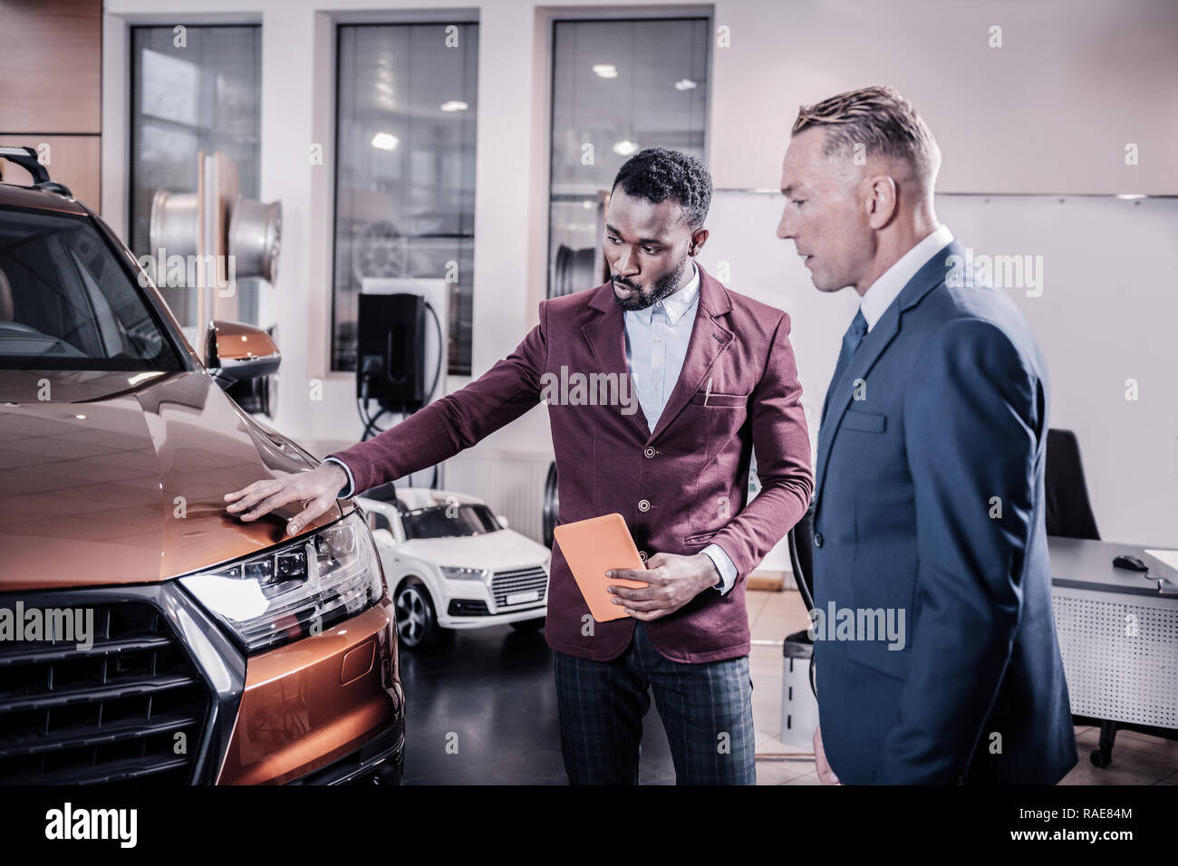 Consultant of car salon telling about the advantages of new car - Stock Image