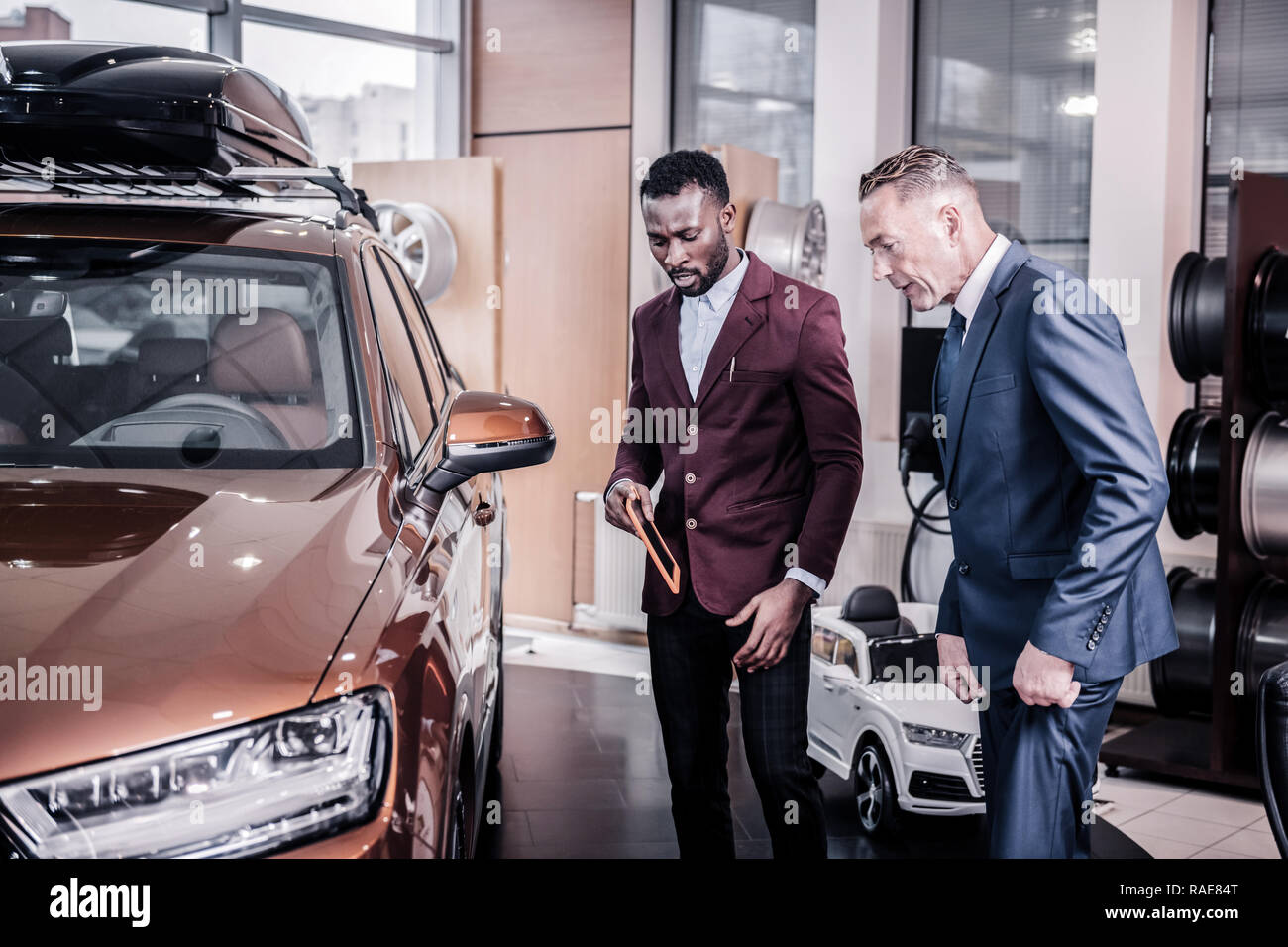 Businessmen standing in car showroom looking at hatchback car - Stock Image
