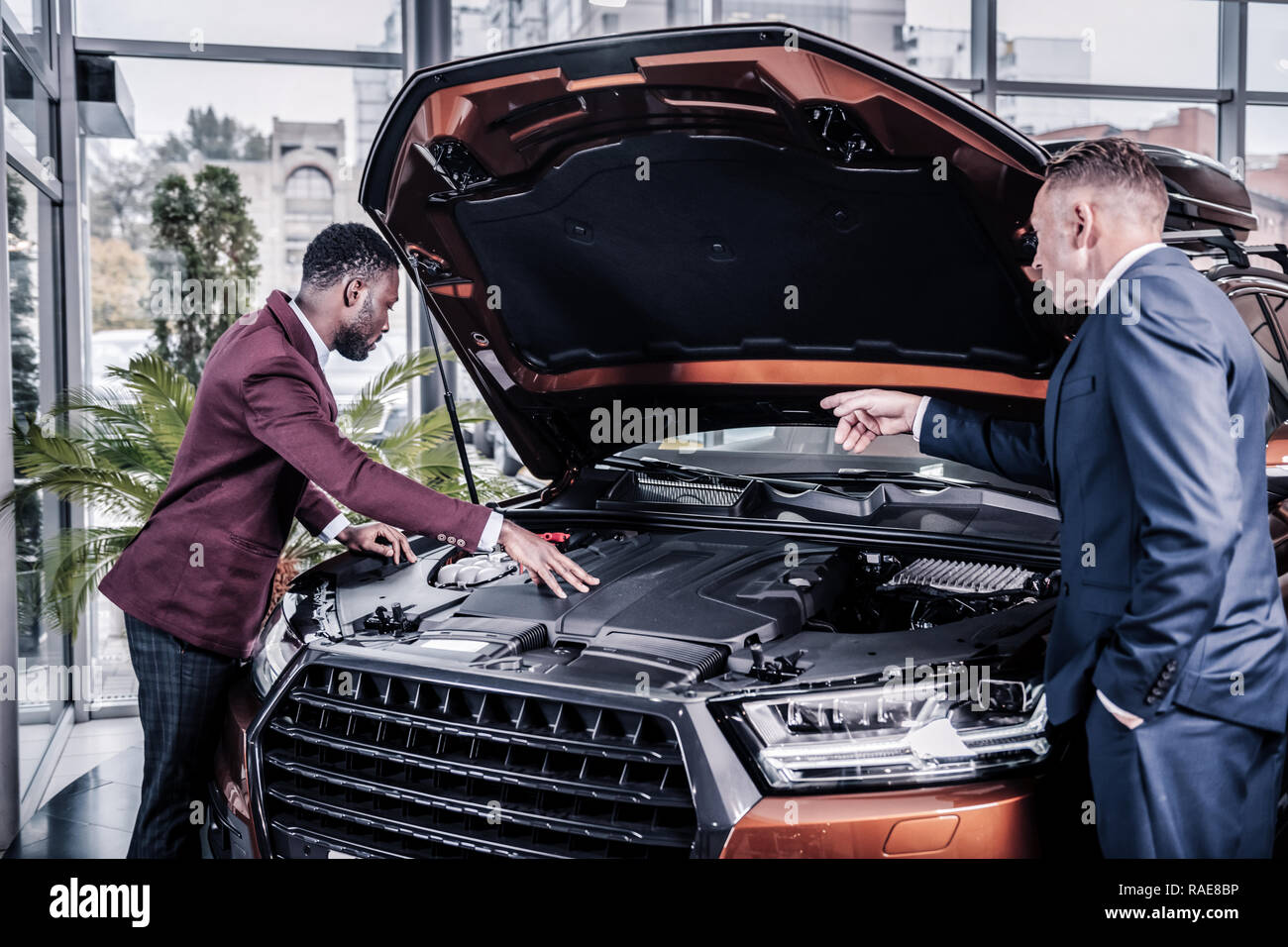 Businessman asking consultant to open front trunk while looking at car - Stock Image