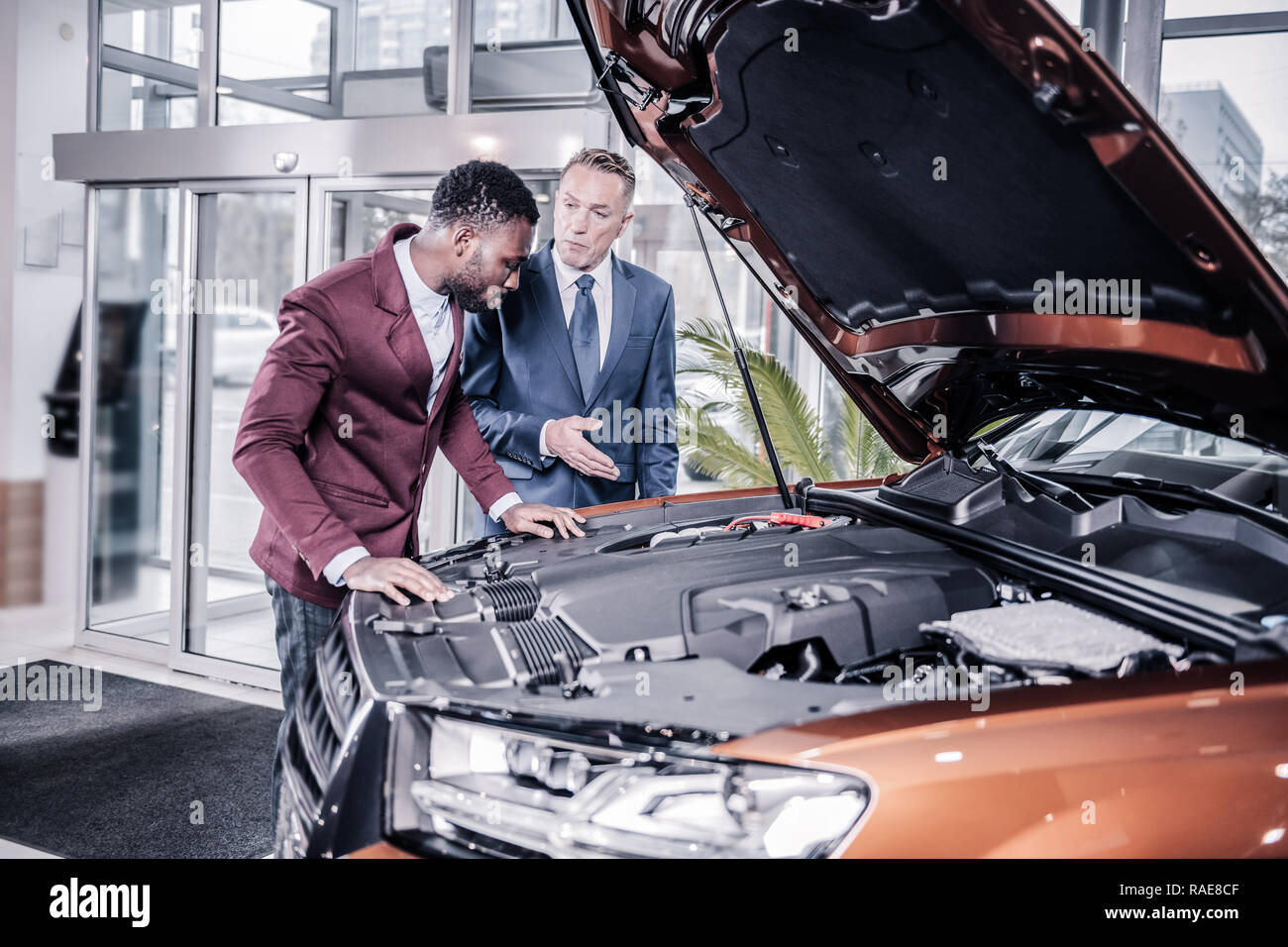 Sales manager of car salon telling about technical characteristics - Stock Image