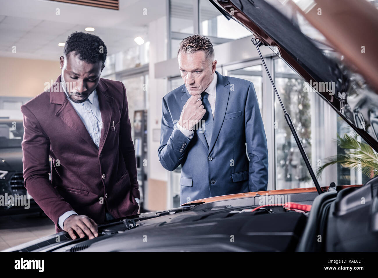 Sales manager wearing dark red jacket standing near client and car - Stock Image