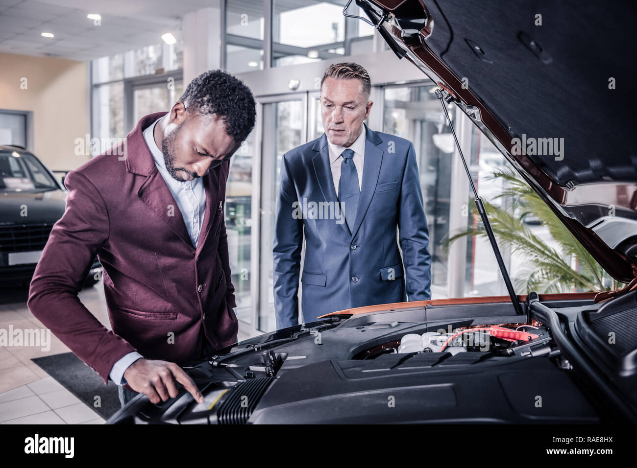 Sales manager of car salon opening front trunk describing car for client - Stock Image