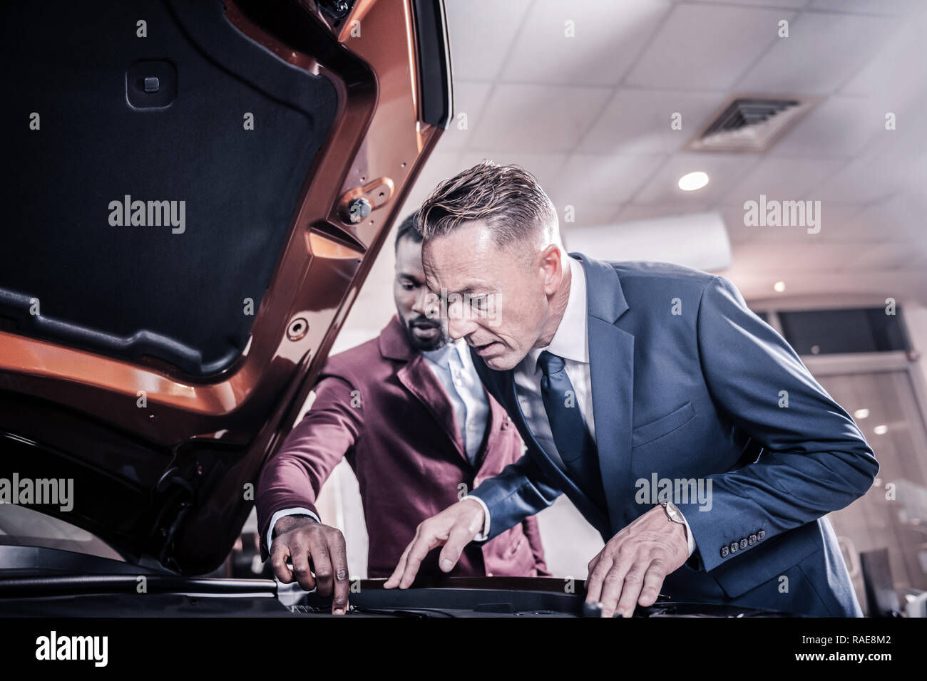 Prosperous man wearing hand watch looking into opened front trunk - Stock Image