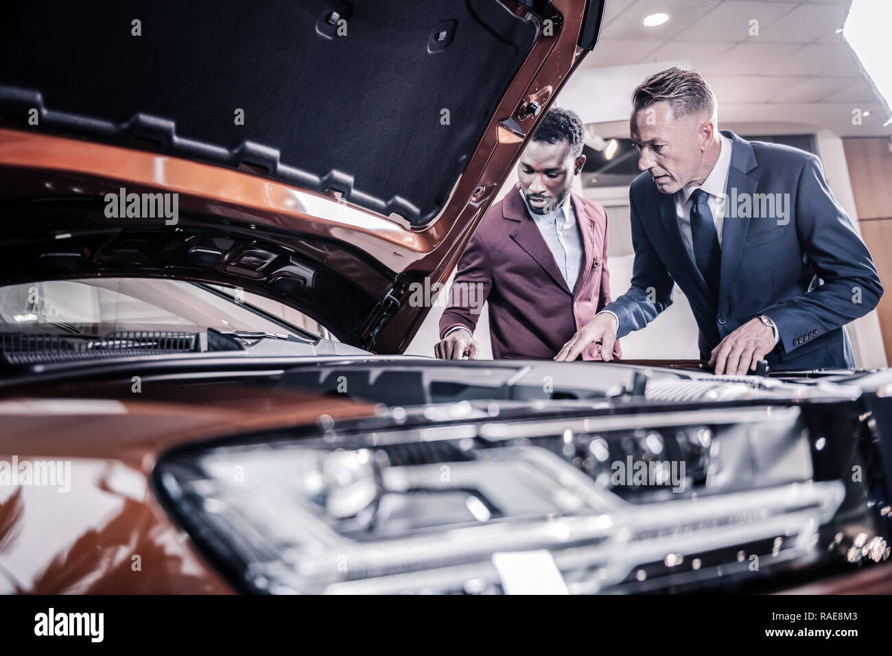 Two men standing near brown hatchback car with opened front trunk - Stock Image