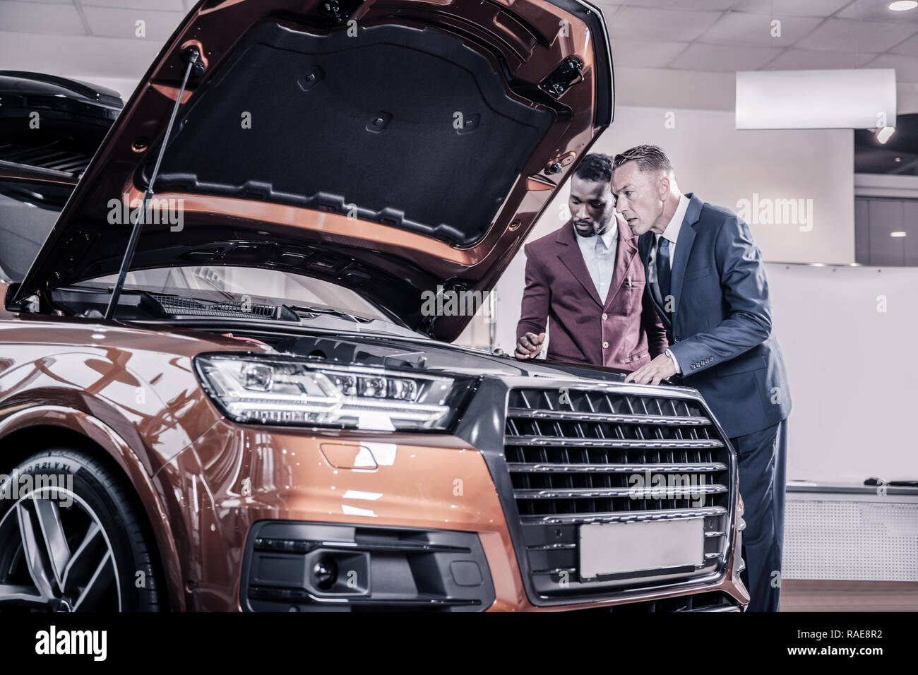 Businessman wearing dark costume looking into opened front trunk - Stock Image