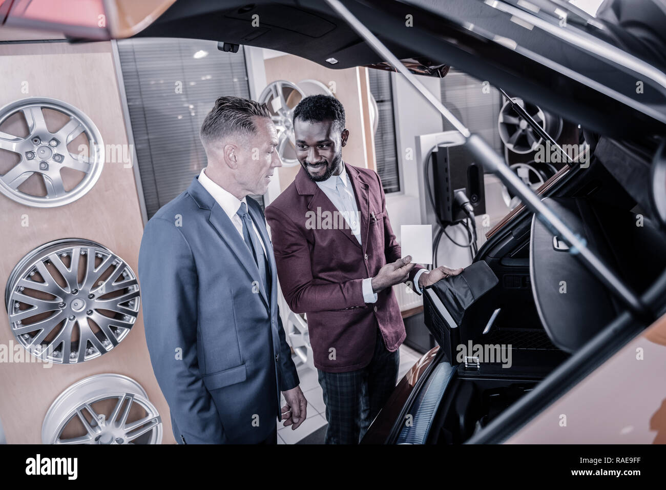 Cheerful sales manager consulting client about new passenger car - Stock Image