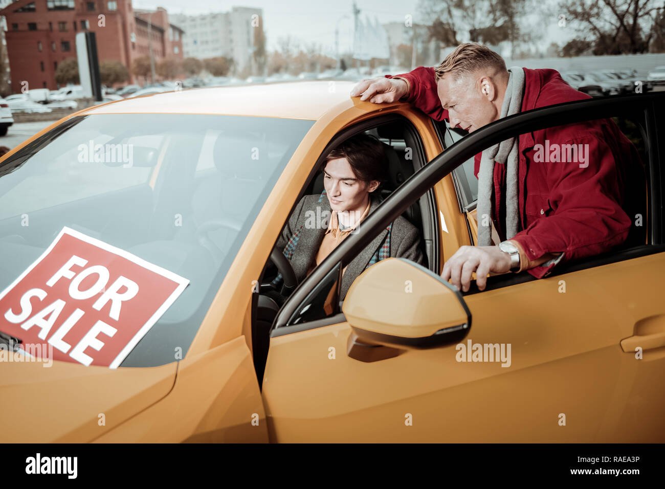 Generous loving father buying new passenger car for son - Stock Image