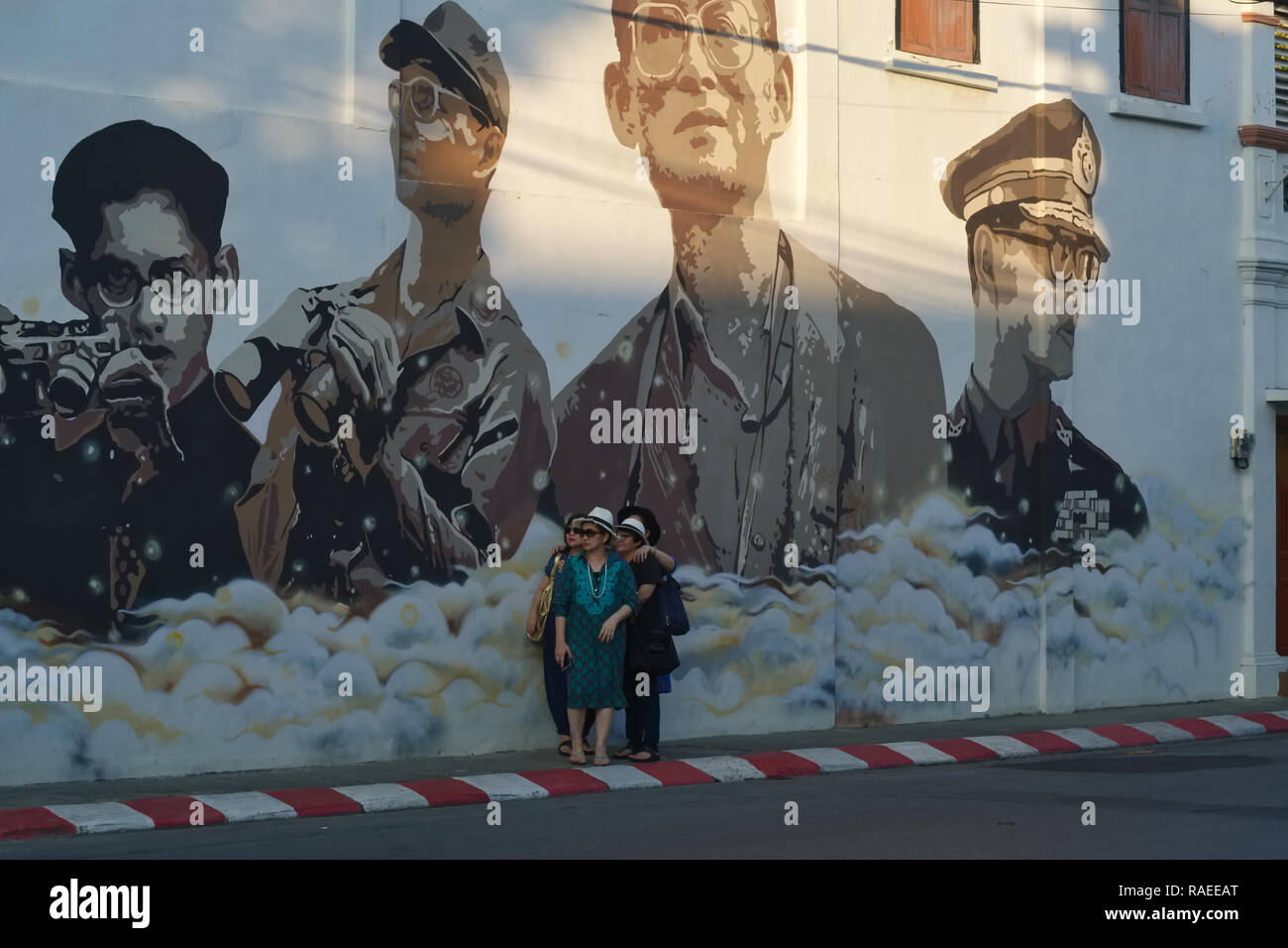 Tourists in Phuket Town, Thailand, pose under a wall painting depicting former Thai King  Bhumipol Adulyadej in different phases of his life - Stock Image