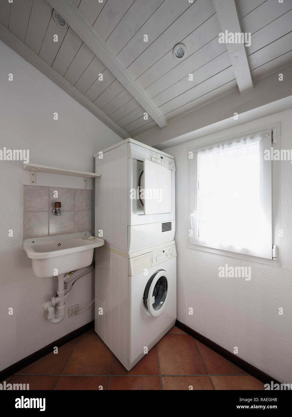 Laundry With Washer And Dryer Stacked On Top Of Each Other Stock