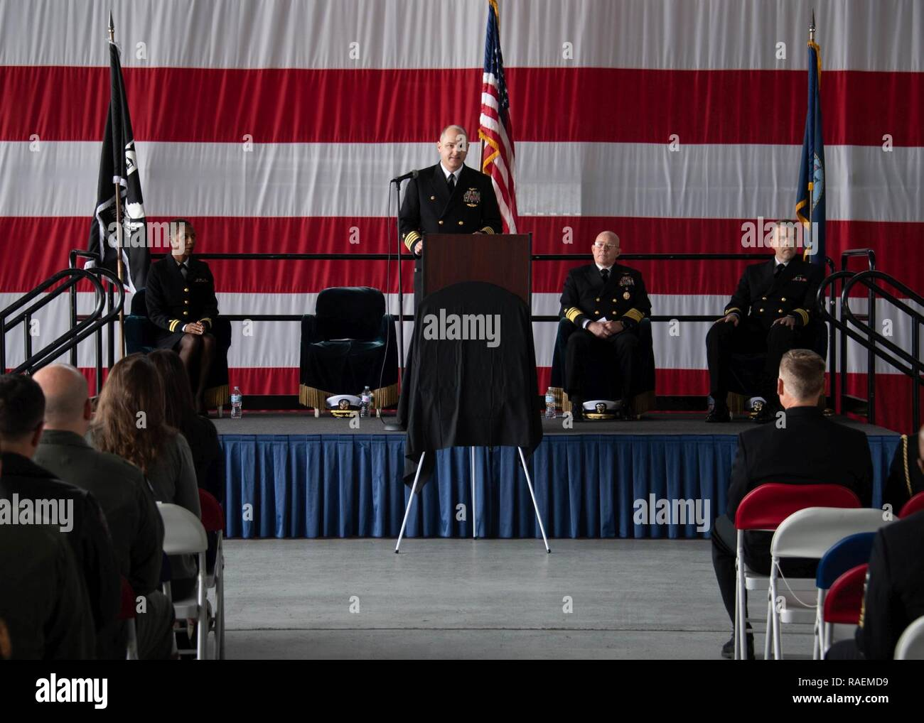 """CORONADO, Calif. (Dec. 14, 2018) Capt. Marcello D. Caceres, Commander, Airborne Command & Control and Logistics Wing, speaks at the establishment ceremony of Fleet Logistics Multi-Mission Squadron 30 """"Titans"""" (VRM-30). VRM-30 is the Navy's first CMV-22B Opsrey squadron and was established to begin the Navy's transition from the C-2A Greyhound. U.S. Navy - Stock Image"""