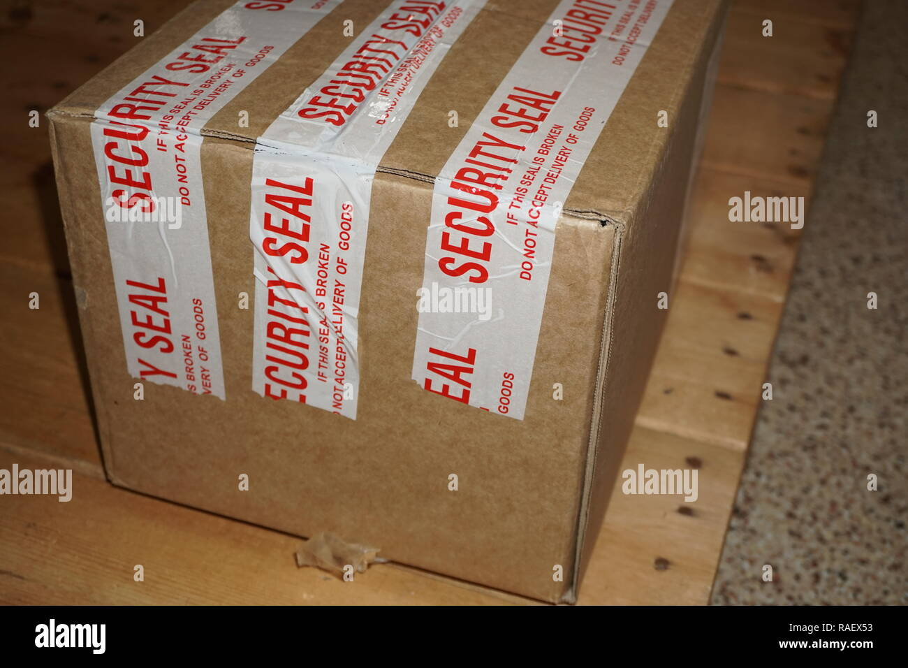 shipping box with security seal tape 'if this seal is broken, do not accept delivery of goods' - Stock Image