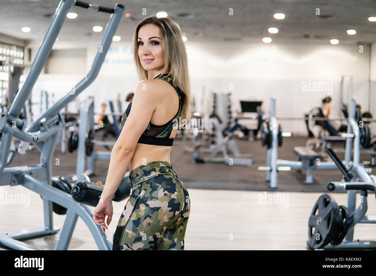 Fitness trainer looks into the camera in the gym - Stock Image