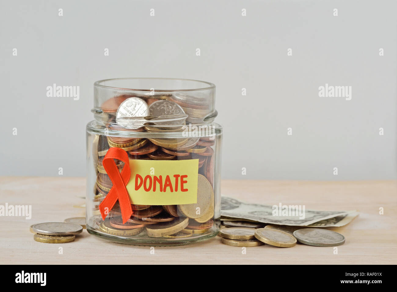 Money jar full of coins with orange ribbon and Donate label - Concept of leukemia, kidney cancer, multiple sclerosis and animal abuse charity - Stock Image