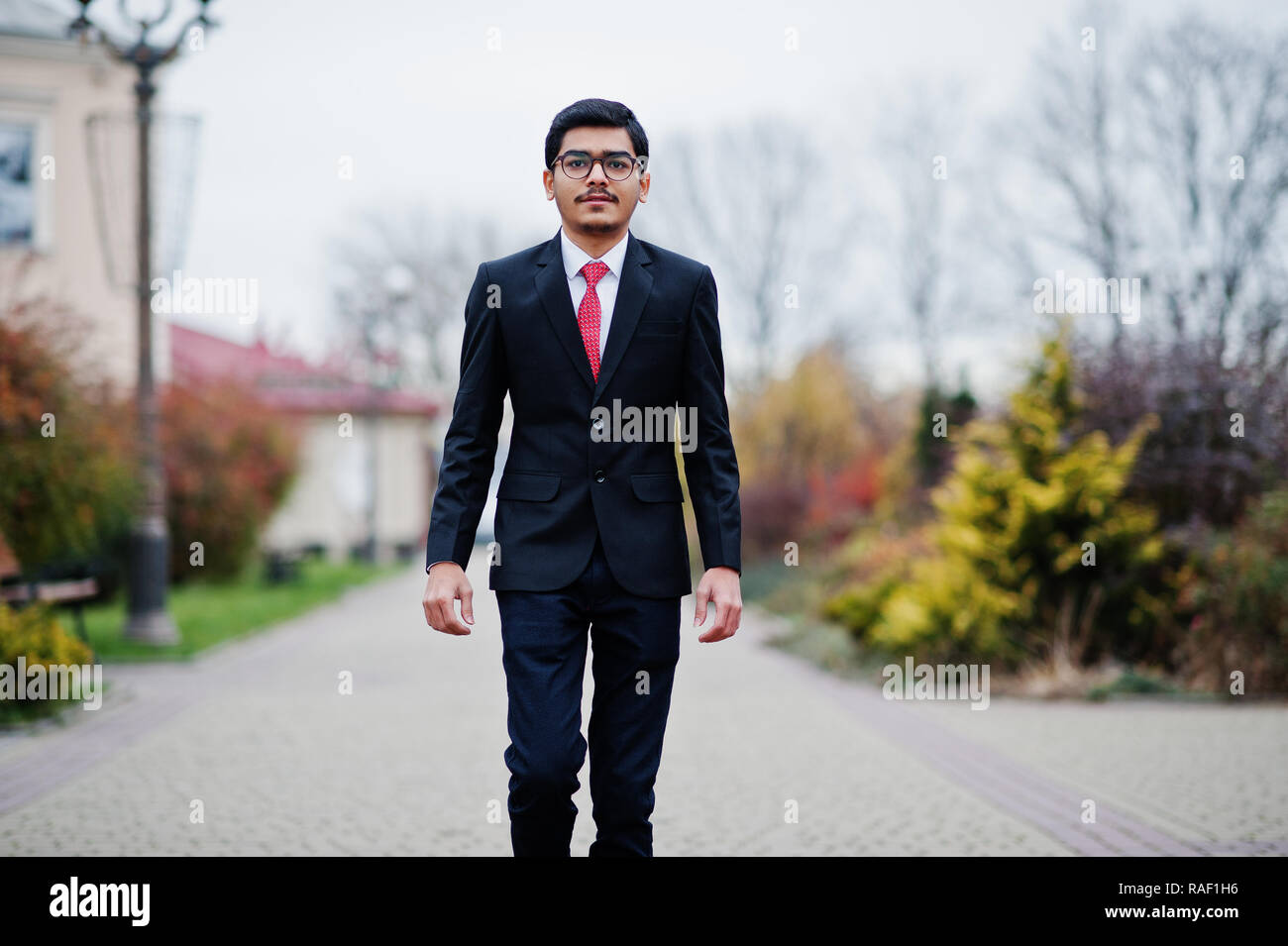 4813e0e194b2 Indian young man at glasses, wear on black suit with red tie posed outdoor.