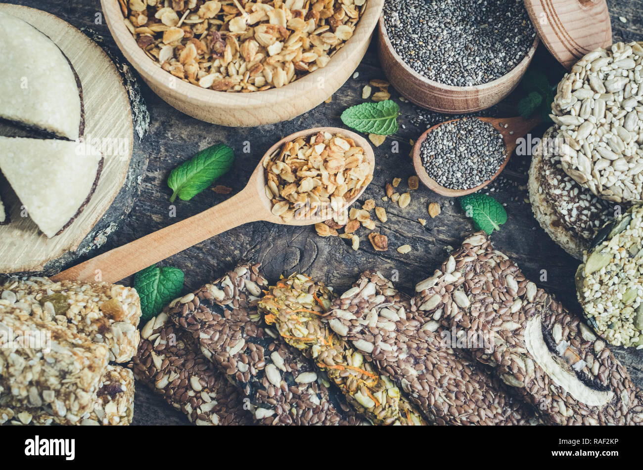 Healthy snacks. Dietary food. Sesame halva. Flakes, chia seeds in two bowls and spoons. Kozinaki, three energy bars and mint. The breadsticks with fla - Stock Image