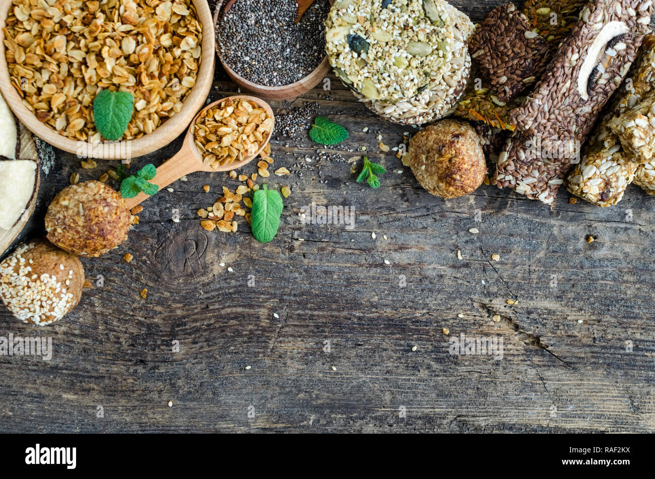 Healthy snacks. Fitness dietary food. Sesame halva. Flakes, chia seeds in two bowls and spoon. Kozinaki, energy bars and the breadsticks. Dietary cook - Stock Image