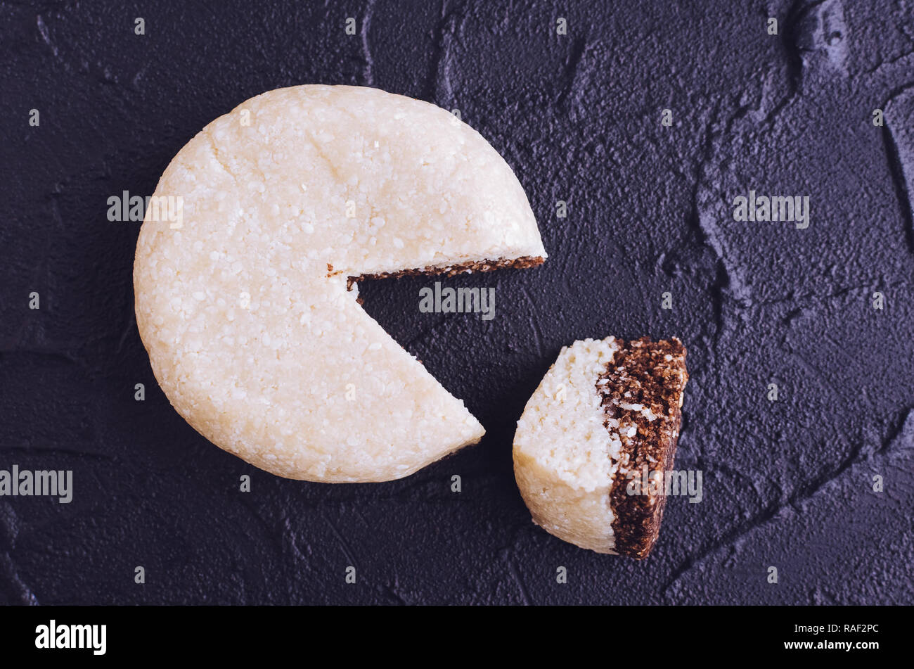Homemade sweet snacks. Fitness dietary food. Sesame halva round form with combined chocolate and protein-egg filler at the shale plate. Vegetarian hea - Stock Image
