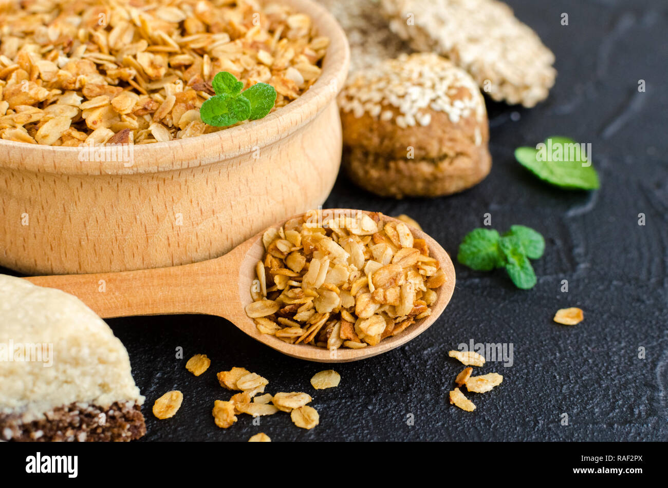 Healthy dessert snacks. Fitness dietary food. Sesame halva. Wooden bowl and spoon with homemade flakes. Oat cookies with sesame. Leafs a mint. Kozinak - Stock Image