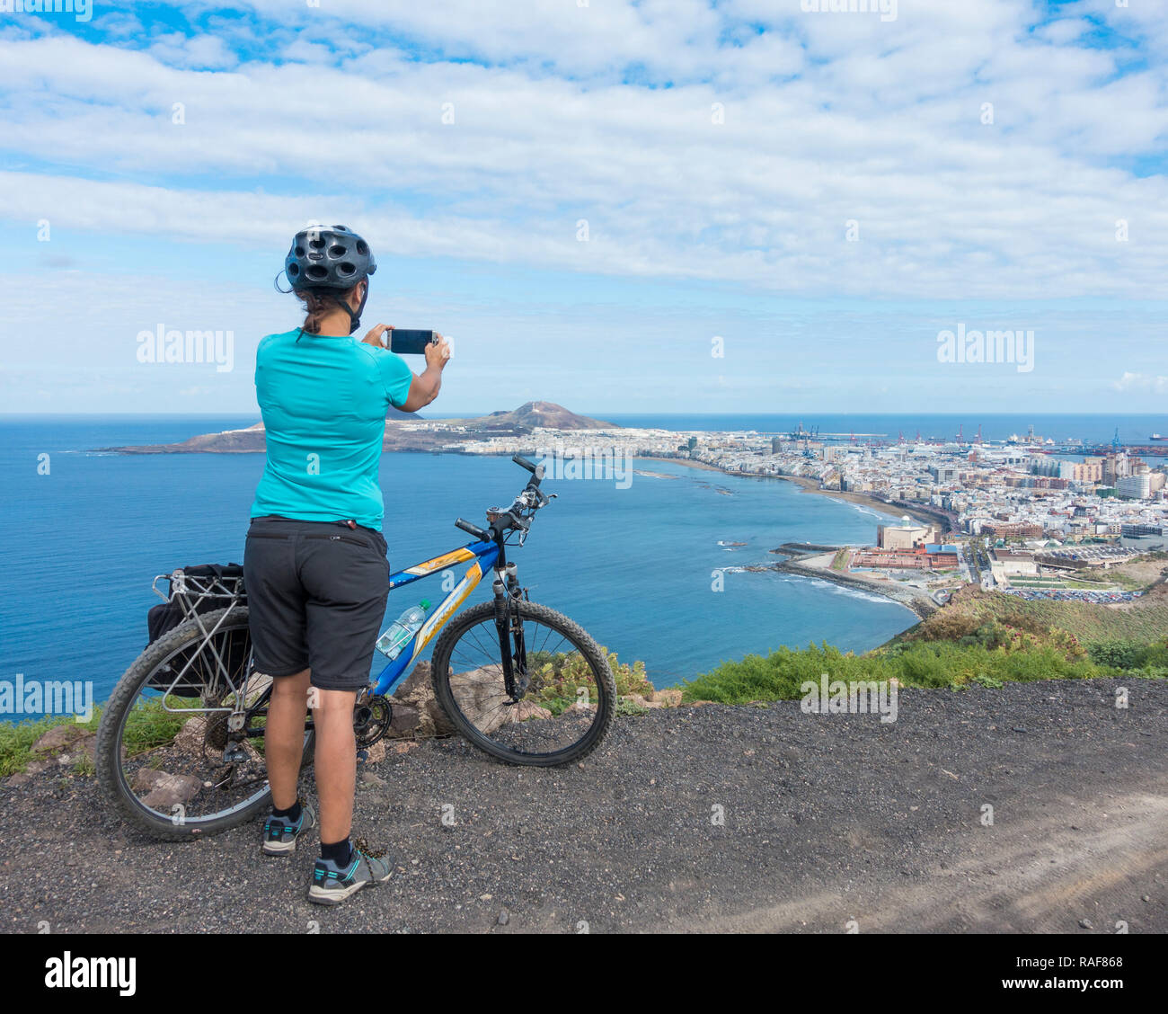 Female mountain biker on mountain overlooking Las Canteras beach and Las Palmas city on Gran Canaria, Canary Islands, Spain - Stock Image