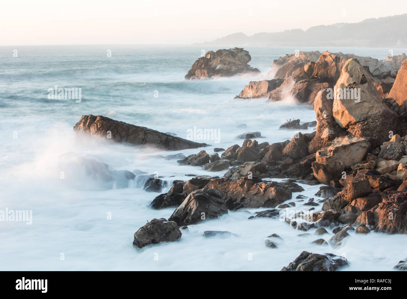 The cold waters of the Pacific Ocean wash against the scenic