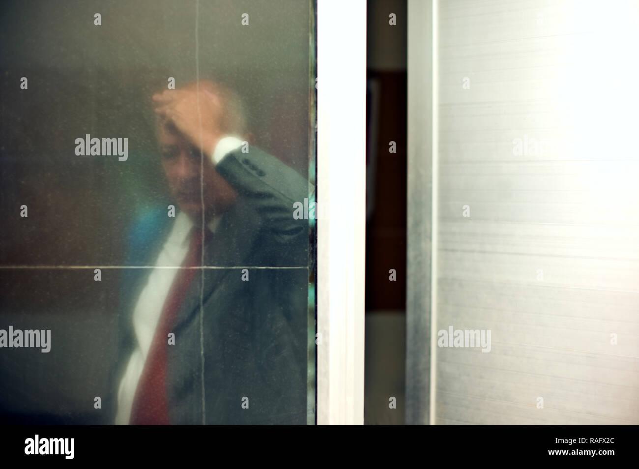 Senior businessman seen through glass door,  looking troubled. - Stock Image