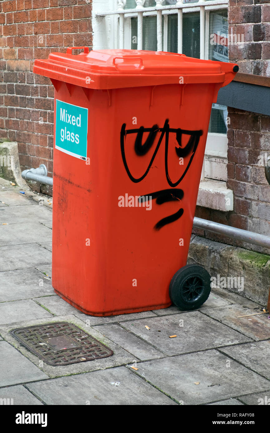 A comical face painted on a glass recycling bin in Bristol, UK. - Stock Image