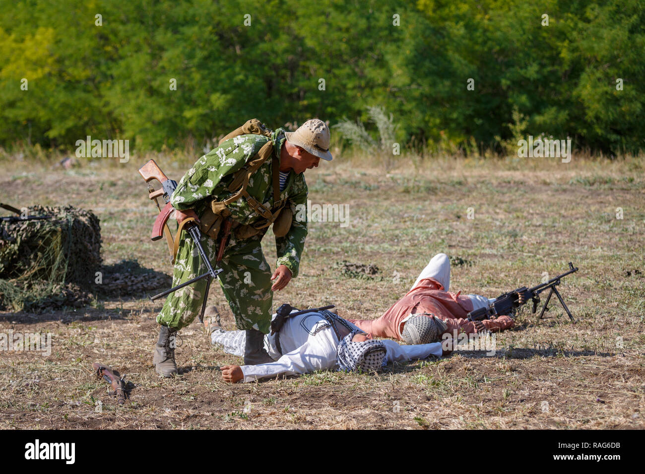 Historical festival Sambek Heights. Soviet soldier with a machine gun in his hands leans over a dead mojahed - Stock Image