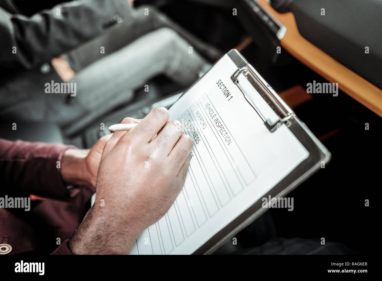 Close up of driving instructor holding pen while making notes - Stock Image