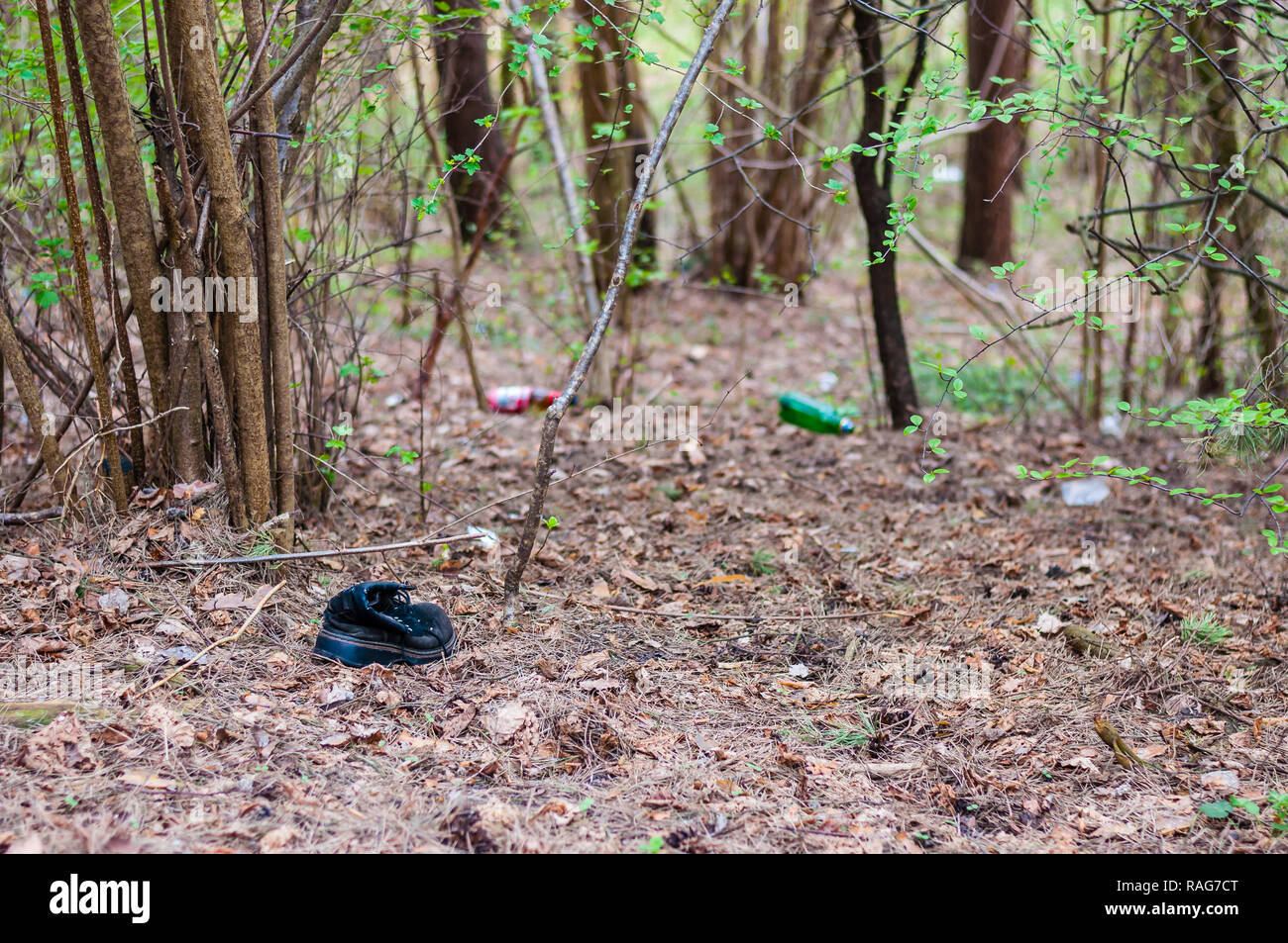 Thrown out boot together with empty alcohol bottles and other trash in the forest - Stock Image