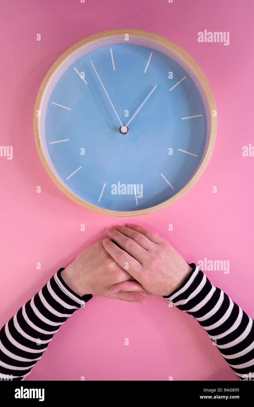 Female hands and large clock on pink background, maternal ageing and menopause, health care and illness prevention concept - Stock Image