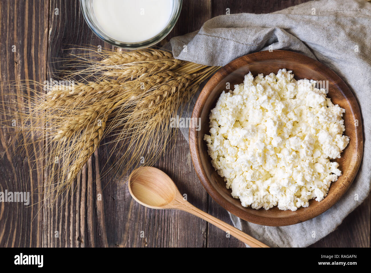 Cottage cheese, milk and ears of wheat on rustic wooden background. Dairy products for jewish holiday Shavuot. Top view. - Stock Image