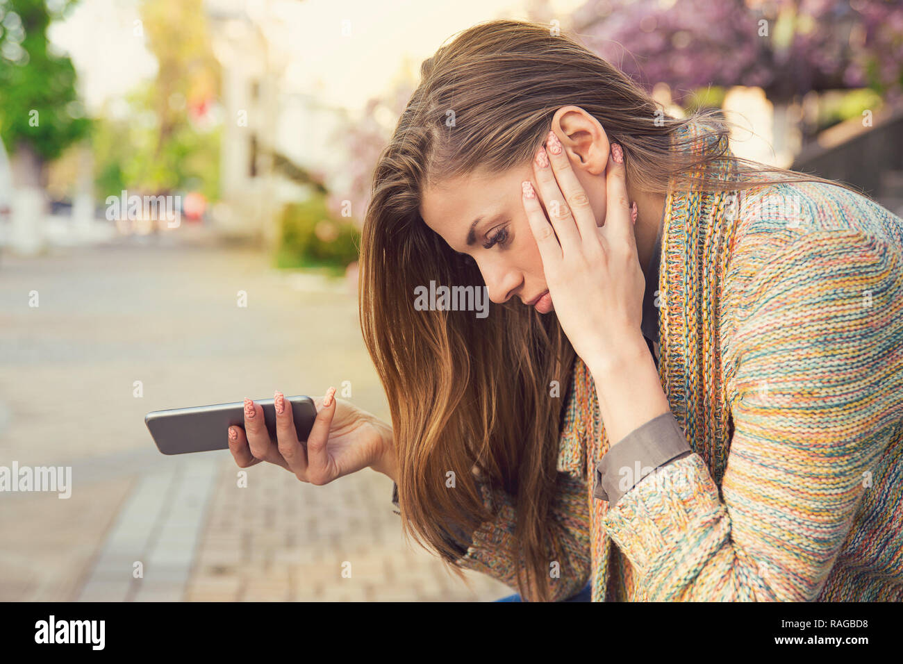 Side view of young woman holding phone and looking happy with breakup while sitting on street - Stock Image
