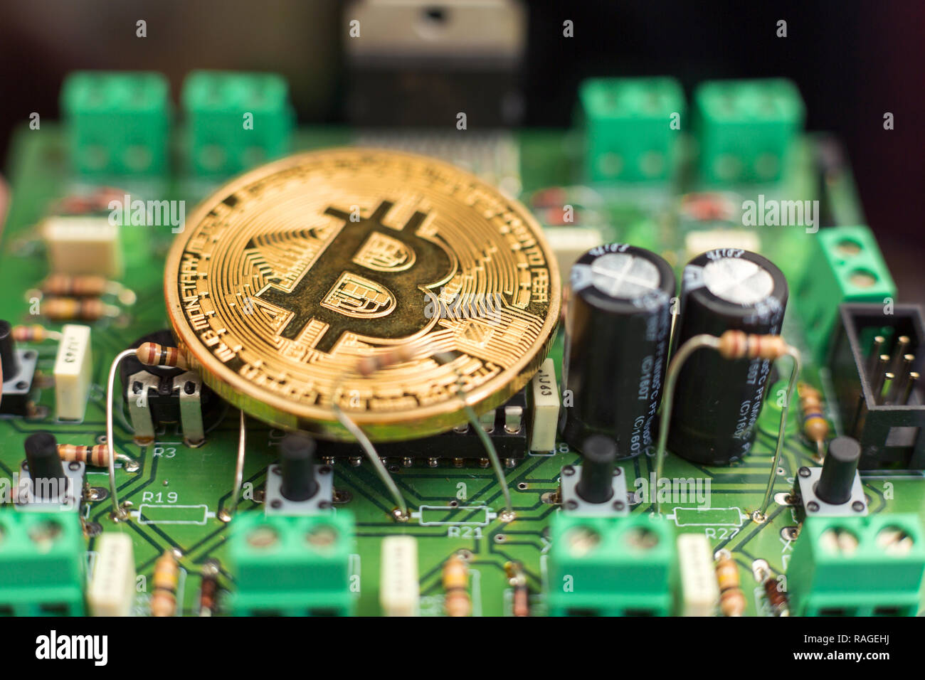 Bitcoin gold coin on computer circuit board microchips. Electronic cryptocurrency. Stock Photo