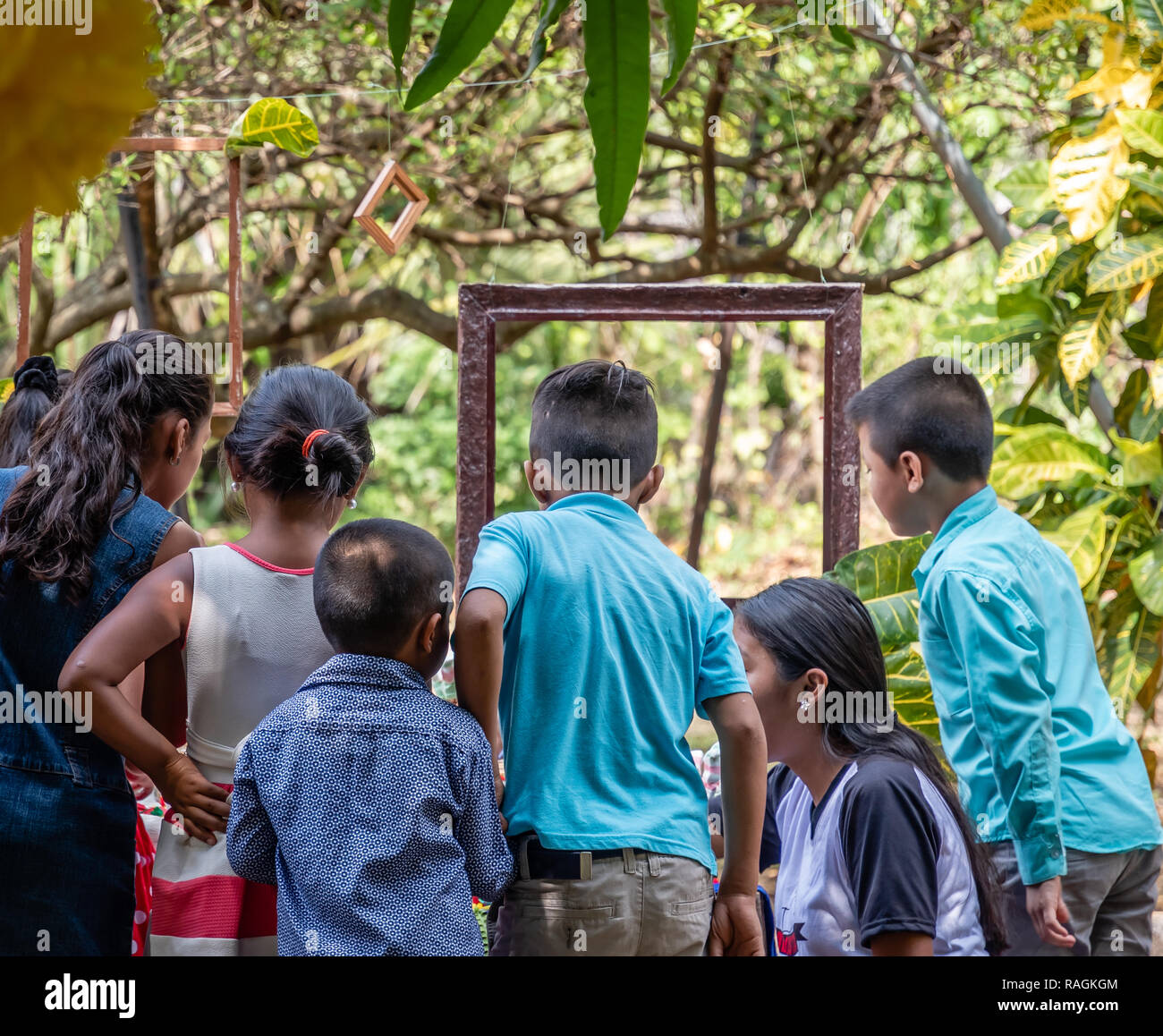 group of latin children looking at something at party in Guatemala Stock Photo