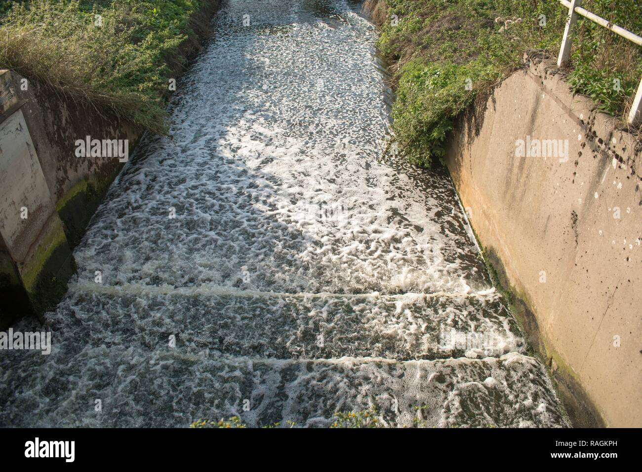 Wastewater discharging from sewage treatment plant into river, West Midlands, UK. - Stock Image