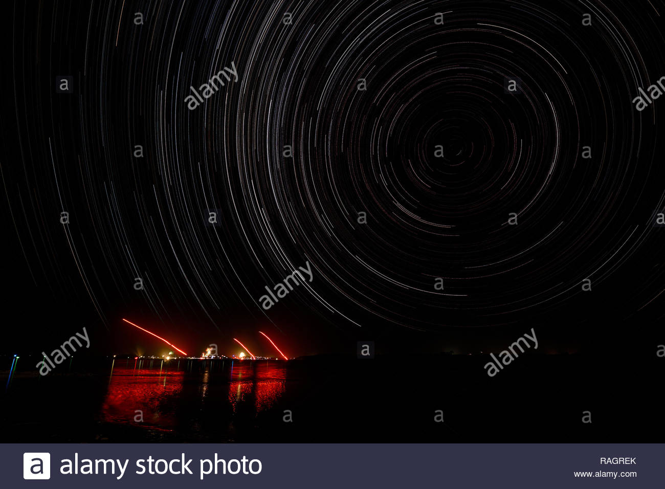 A wide-angled star-trail image, depicting the south celestial pole and fireworks;  above the Australian coastal town of Yamba, New Year's Eve 2018. - Stock Image