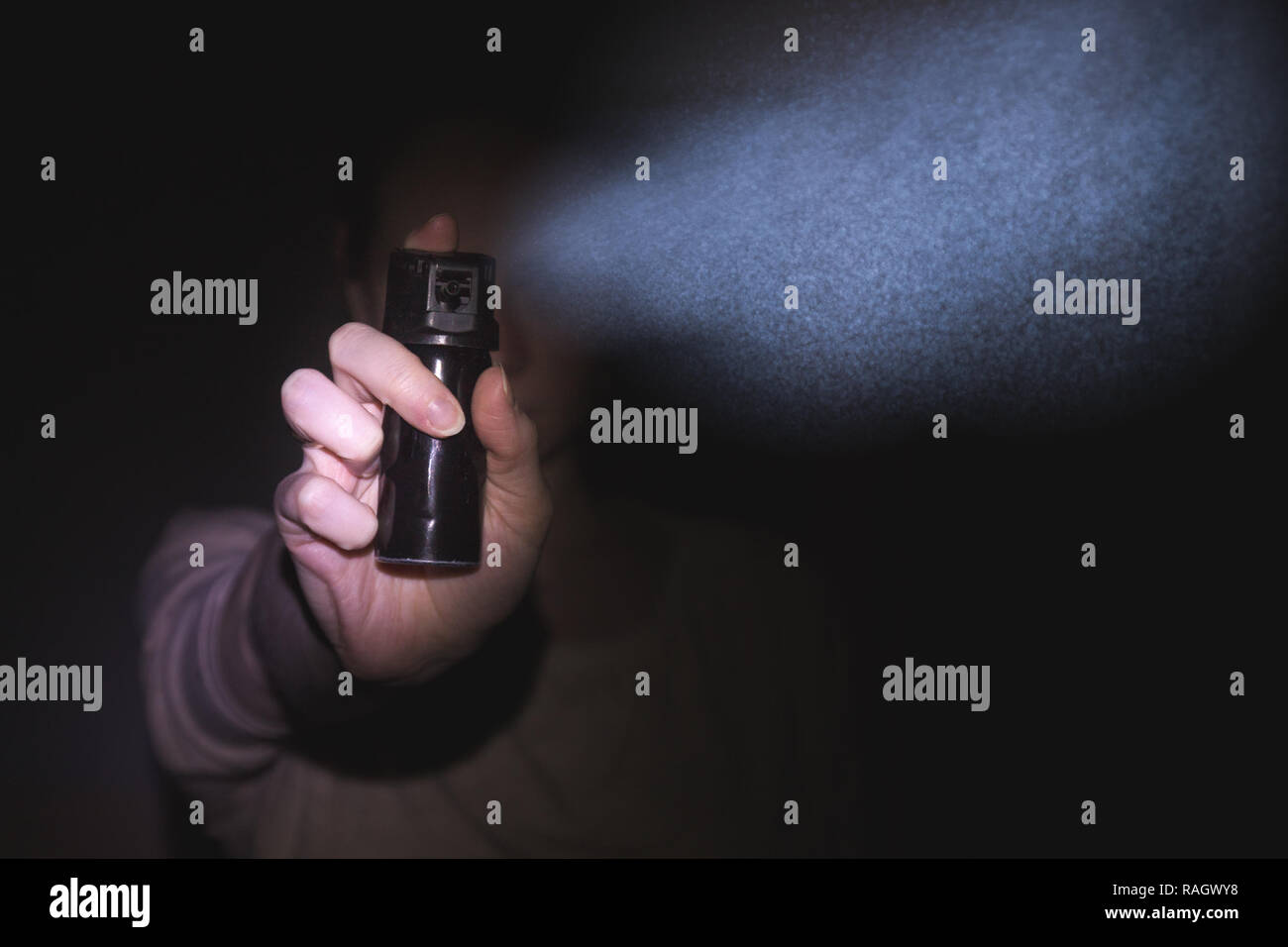 a woman is protected by a gas pepper spray in the dark, a black  - Stock Image
