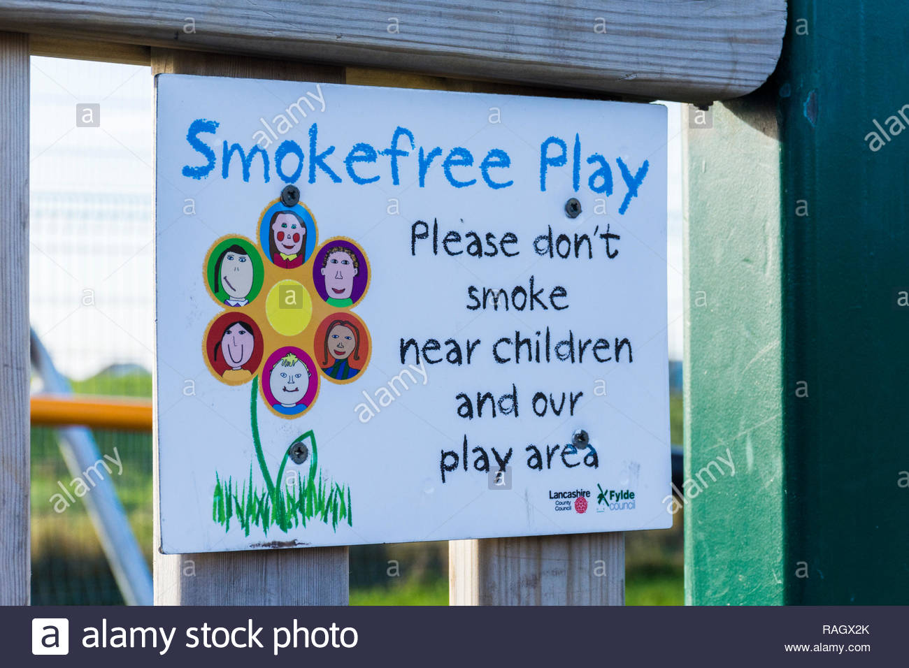 Sign on the gate of a play area requesting smokefree play and that people don't smoke near children and the play area Stock Photo
