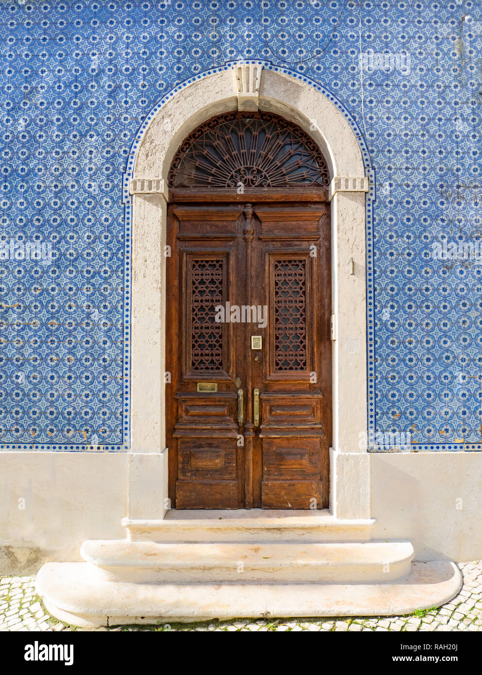 Lisbon - Portugal, facade of a house covered with typical blue tiles, azulejos, and ancient decorated wooden door - Stock Image