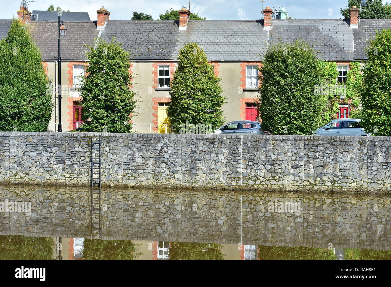Row of typical narrow townhouses behind stone wall on bank of river Nore in Kilkenny. - Stock Image