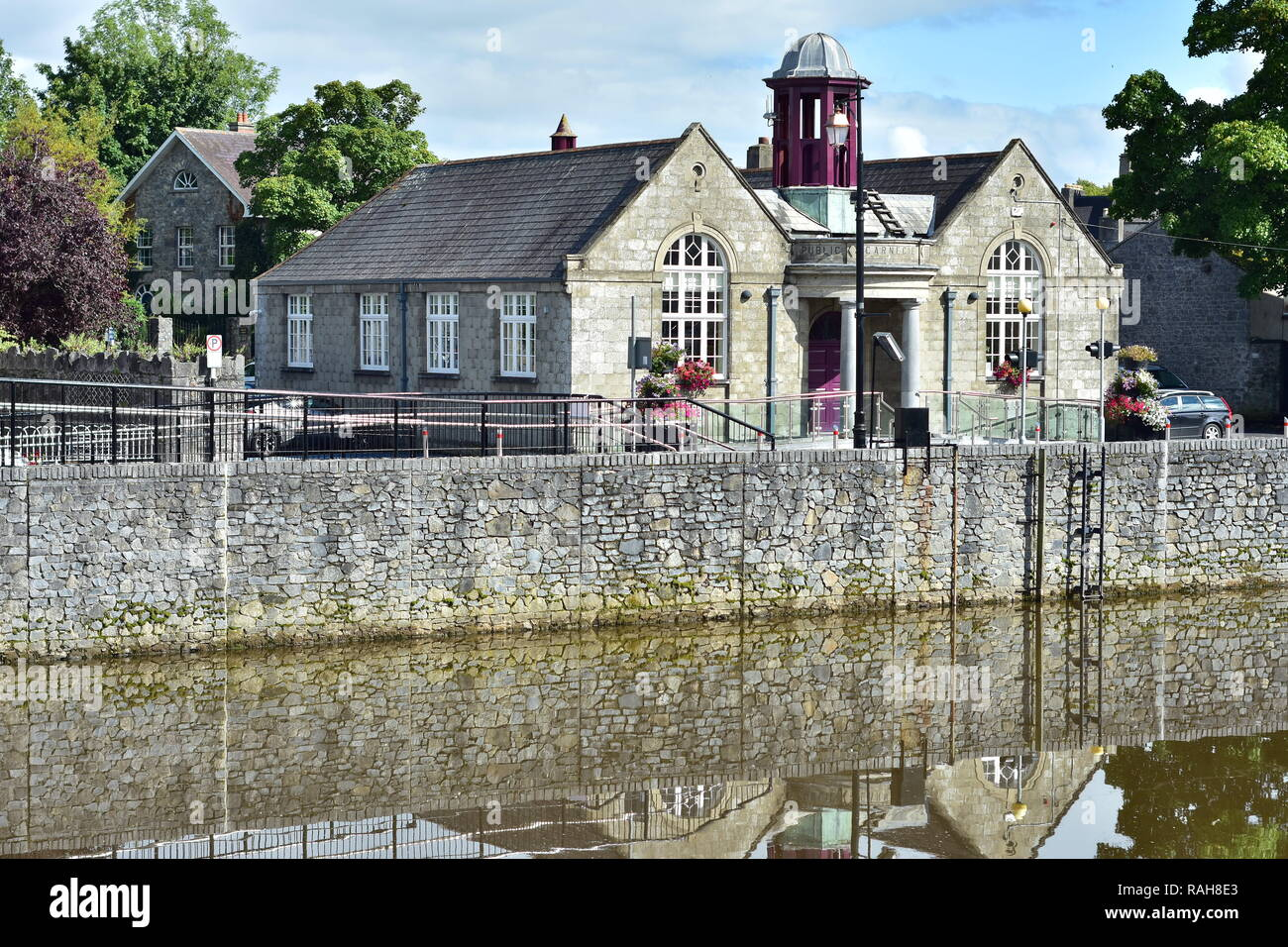 Kilkenny City Branch Library stone building with purple tower on bank of river Nore. - Stock Image