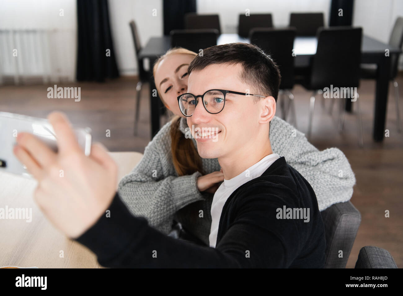 Young friends photographing themselves with mobile phone in a cafe Stock Photo