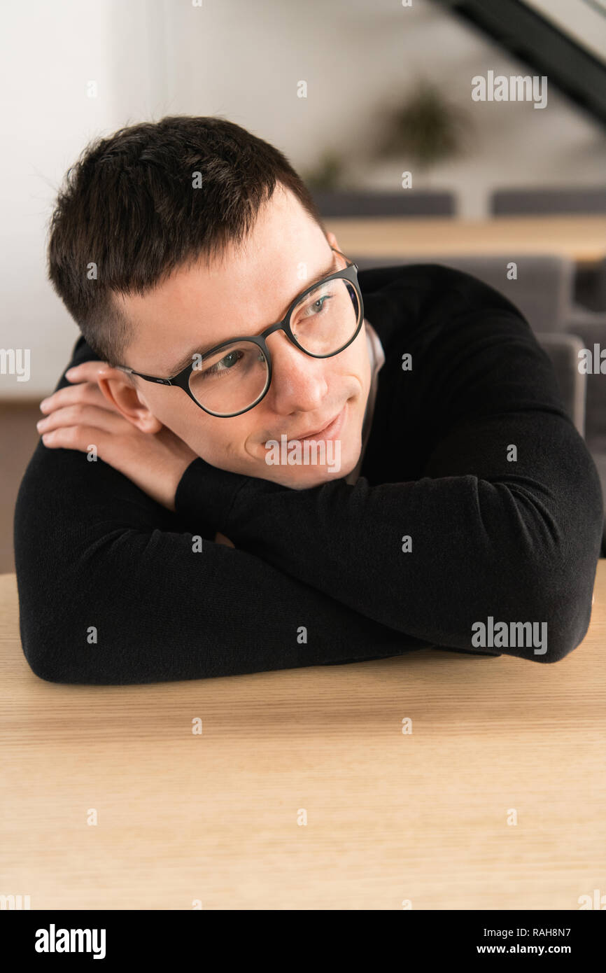 Portrait of pensive dreamy hipster guy imagines something in his mind, looks aside, being deep in thoughts. Attractive hipster guy dreams about vacations or weekends alone - Stock Image