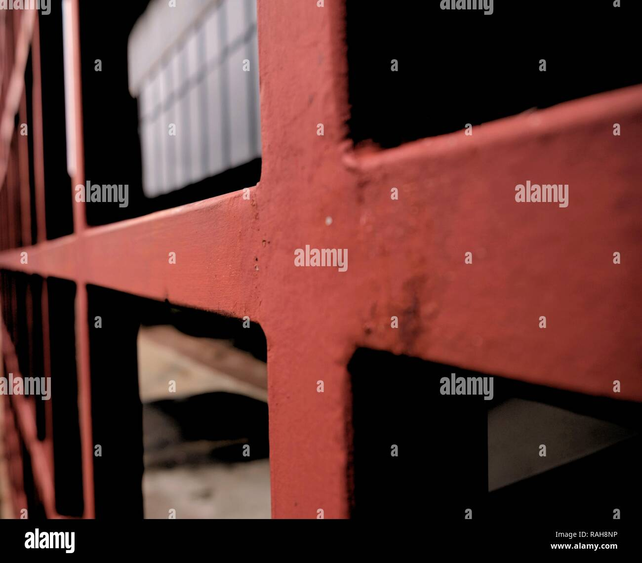 Close-up of a red metal square pattern; exterior design element at an office building. - Stock Image